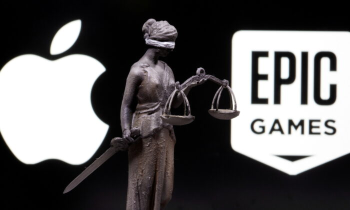 3D printed Lady Justice figure is seen in front of displayed Apple and Epic Games logos in this illustration photo taken on Feb. 17, 2021. (Dado Ruvic/Illustration/Reuters)