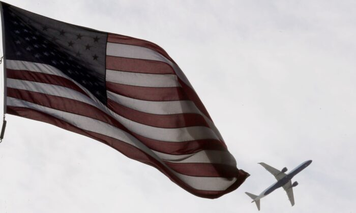 A Delta Airlines flight takes off past a U.S. flag in Boston, Mass., on May 27, 2021. (Brian Snyder/Reuters)