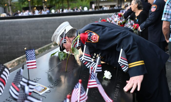 Retired Paramedic Chief Charlie Wells kisses the name of a relative killed in the attack on the World Trade Center at the National 9/11 Memorial & Museum during a ceremony commemorating the 20th anniversary of the 9/11 attacks in New York, on Sept. 11, 2021. (David Handschuh/AFP/Getty Images)