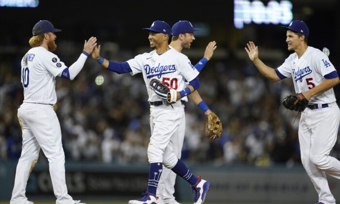 From left, Los Angeles Dodgers third baseman Justin Turner (10), right fielder Mookie Betts (50), second baseman Trea Turner (6), and shortstop Corey Seager (5) celebrate after a 3-0 win over the San Diego Padres in a baseball game Friday, Sept. 10, 2021, in Los Angeles. (Ashley Landis/AP Photo)