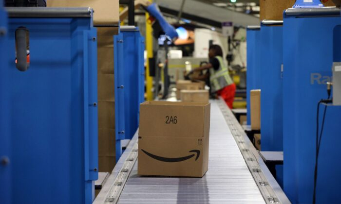 Workers fill boxes to ship at an Amazon fulfillment center in Romeoville, Ill., on Aug. 1, 2017. (Brian Cassella/Chicago Tribune/TNS)
