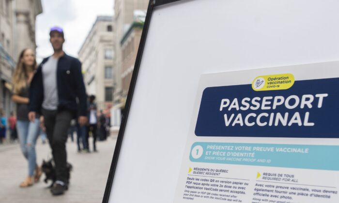 A sign outside a restaurant in Montreal advising customers of the Quebec government's newly implemented COVID-19 vaccine passport, on Sept. 6, 2021. (The Canadian Press/Graham Hughes)