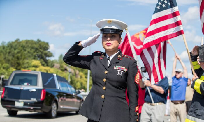 U.S. Marine Ssgt. Alice Ward stands at attention on the side of I-93 North as the hearse carrying fallen Marine Sgt. Johanny Rosario Pichardo passes in Stoneham, Mass., on Sept. 11, 2021.  (Scott Eisen/Getty Images)