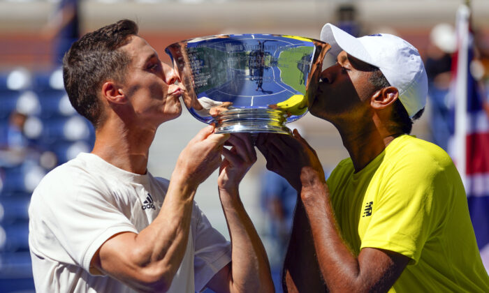 Men's doubles champions Joe Salisbury of Great Britain (L) and Rajeev Ram of the United States pose with the trophy on day twelve of the 2021 U.S. Open tennis tournament at USTA Billie Jean King National Tennis Center in Flushing, New York, on Sept. 10, 2021. (Danielle Parhizkaran/USA TODAY Sports via Reuters)