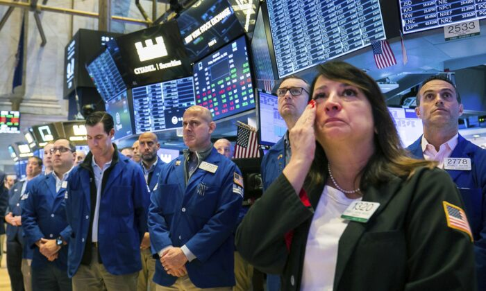 Floor traders, including Phyllis Arena Woods (R), gather in remembrance on the eve of Sept. 11, on the Exchange trading floor, on Sept. 10, 2021. (Courtney Crow/New York Stock Exchange via AP)