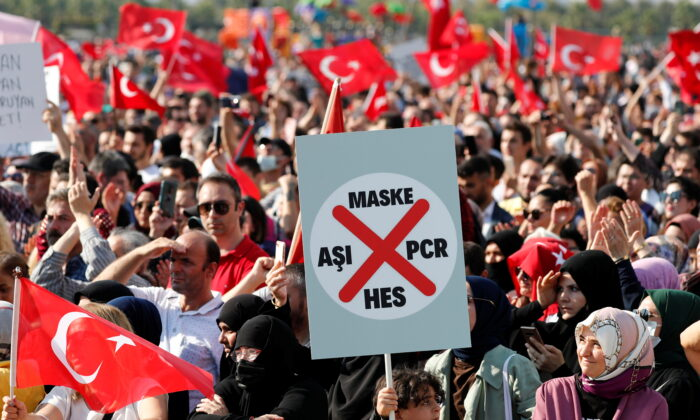 A boy holds a placard as demonstrators wave Turkish flags during a protest against official COVID-19-related mandates, including vaccinations, tests, and masks, in Istanbul, Turkey, on Sept. 11, 2021. (Murad Sezer/Reuters)