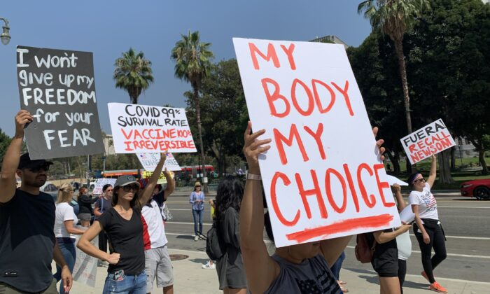 People hold signs in front of the Los Angeles Police Department (LAPD) headquarters to protest the government's policy of forcing frontline workers to be vaccinated against the CCP virus on Sept. 8, 2021. (Linda Jiang/The Epoch Times)