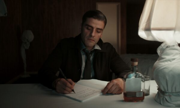 man writing and drinking