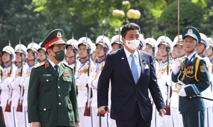 Vietnamese Defense Minister Phan Van Giang (L) and Japanese Defense Minister Nobuo Kishi review honor guards in Hanoi, Vietnam, on Sept. 12, 2021.  (Nguyen Trong Duc/VNA via AP)