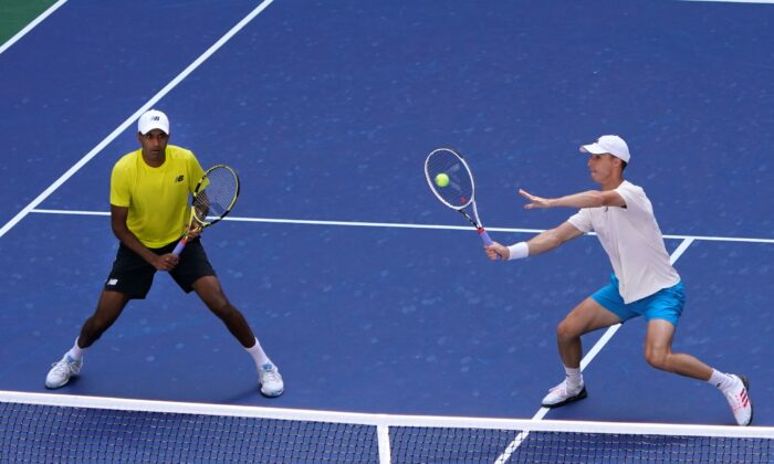 Joe Salisbury, of Great Britain, returns the ball as teammate Rajeev Ram, of the United States, watches during their men's doubles final match against Bruno Soares, of Brazil, and Jamie Murray, of Great Britain, at the U.S. Open tennis championships in New York on Sept. 10, 2021. (Elise Amendola/AP Photo)