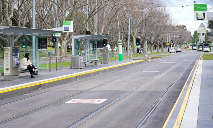 A lone passenger sits at a tram stop on a mostly-empty city center street on the first day of a lockdown in Melbourne, Australia, on July 16, 2021. (Sandra Sanders/Reuters)