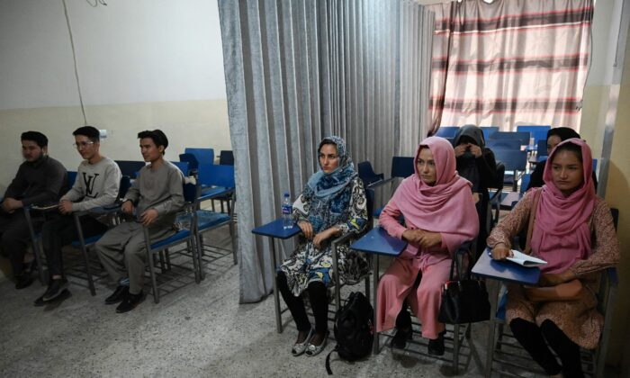 Students attend a class bifurcated by a curtain separating males and females at a private university to follow the Taliban's ruling, in Kabul on Sept. 7, 2021. (Aamir Qureshi/AFP via Getty Images)