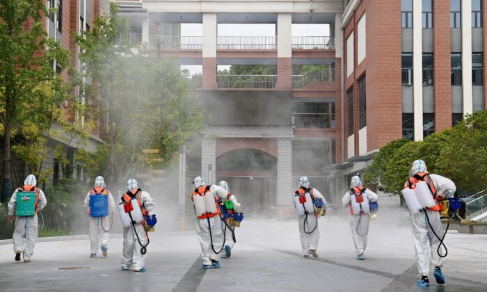 Workers in protective suits disinfect the compound of a primary school before schools reopen for the upcoming semester, in Wuhan, Hubei province, China, on Aug. 25, 2021. (China Daily via Reuters)