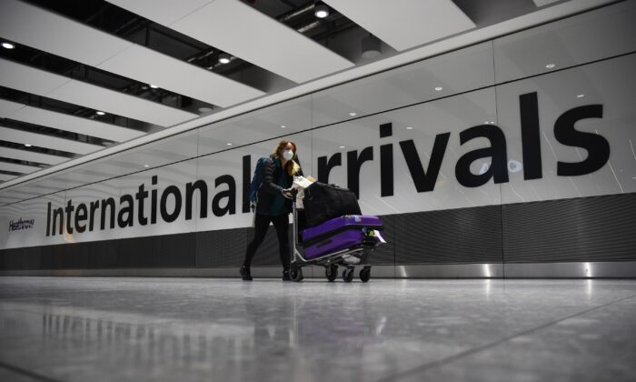 A passenger pushing luggage through the Arrival Hall of Terminal 5 at London's Heathrow Airport on Jan. 18, 2021. (Kirsty O'Connor/PA)