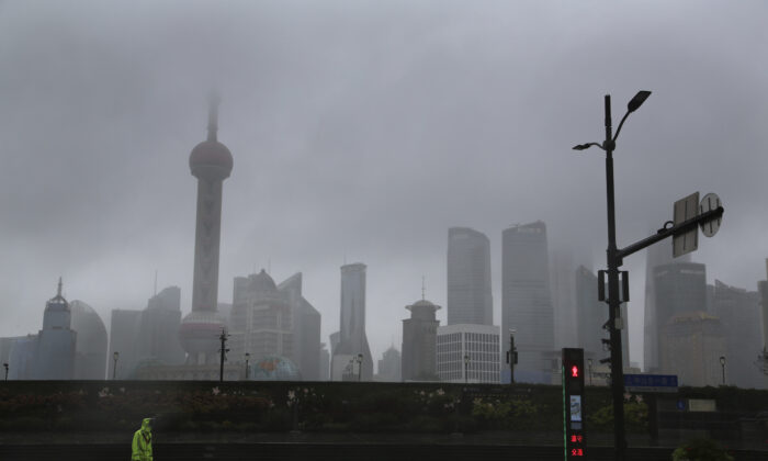 A traffic policeman works near the bund overlooking the skyline in Shanghai, China, on Sept. 13, 2021. (Chen Si/AP Photo)
