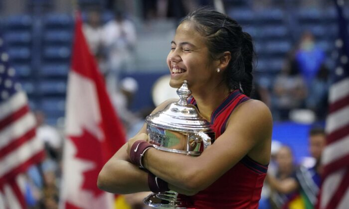 Emma Raducanu, of Britain, hugs the U.S. Open championship trophy after defeating Leylah Fernandez, of Canada, during the women's singles final of the U.S. Open tennis championships on Sept. 11, 2021, in New York. (Elise Amendola/AP Photo)