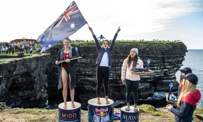 (L-R): Jessica Macaulay of Canada, Rhiannan Iffland, and Xantheia Pennisi of Australia celebrate on the podium during the final competition day of the fourth stop of the Red Bull Cliff Diving World Series at Downpatrick Head, Ireland, on Sept. 12, 2021. (Dean Treml/Red Bull Content Pool via Reuters)