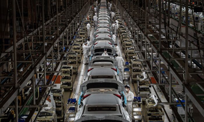 Employees work on an assembly line at an auto plant of Dongfeng Honda in Wuhan in China's central Hubei Province on March 23, 2020. (STR/AFP)