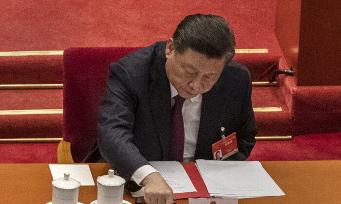 China's Leader Xi Jinping presses a button to vote in favor of a resolution to overhaul Hong Kong's electoral system at the Great Hall of the People in Beijing, on March 11, 2021. (Kevin Frayer/Getty Images)