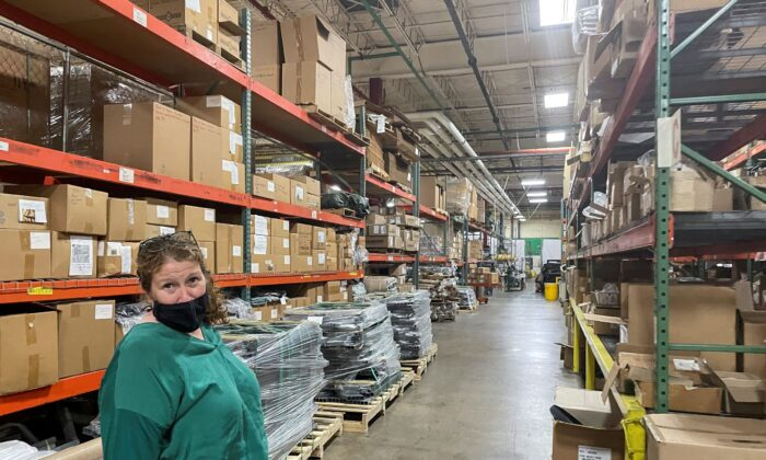 Diamond Brand COO Lauren Rash stands in an aisle of shelves with stockpiled parts as the 'lean' supply management has been upended by global shortages and bottlenecks, at Diamond Brand factory in Fletcher, outside Asheville, N.C., on Aug. 11, 2021. (Howard Schneider/Reuters)
