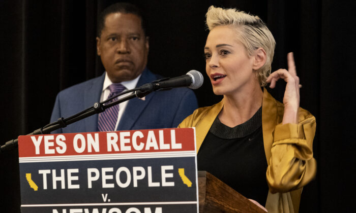Republican conservative radio talk show host Larry Elder, left, listens as former actress and activist Rose McGowan speaks as the pair hold a news conference at the Luxe Hotel Sunset Boulevard in Los Angeles on Sept. 12, 2021. McGowan, who was one of the earliest of dozens of women in the #MeToo movement to accuse Hollywood producer Harvey Weinstein of sexual misconduct, has endorsed Elder for governor in California's recall election. (AP Photo/Damian Dovarganes)
