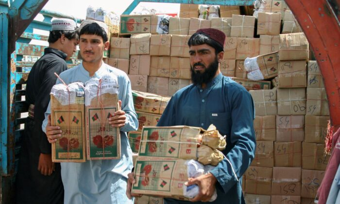 People unload boxes of pomegranates from Afghanistan, from a truck at the 'Friendship Gate' crossing point, in the Pakistan-Afghanistan border town of Chaman, Pakistan, on Sept. 7, 2021. (Saeed Ali Achakzai/Reuters)