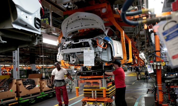 General Motors assembly workers connect a battery pack underneath a partially assembled 2018 Chevrolet Bolt EV vehicle on the assembly line at Orion Assembly in Lake Orion, Mich., on March 19, 2018. (Rebecca Cook/Reuters)
