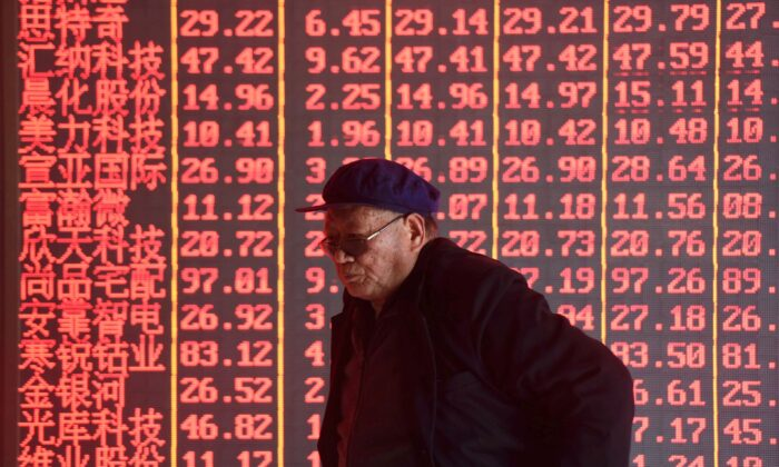 A man stands in front of an electronic board displaying stock information at a brokerage firm in Hangzhou, Zhejiang Province, China on April 1, 2019. (Stringer/Reuters)