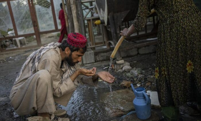 A displaced Afghan man drinks from a water tank at an internally displaced persons camp in Kabul, Afghanistan, on Sept. 13, 2021. (Bernat Armangue/AP Photo)