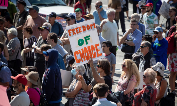 People listen to a speaker during a rally and march organized by those opposed to COVID-19 vaccination passports and public health measures, in Vancouver, on Sept. 8, 2021. (The Canadian Press/Darryl Dyck)