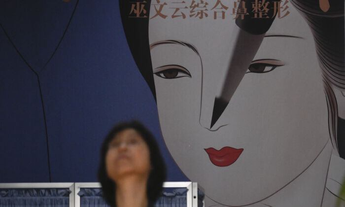 A woman walks past a large display at a plastic surgery clinic in Beijing on July 15, 2021. (Wang Zhao/AFP)