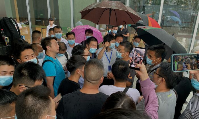 People gather outside the Evergrande headquarters in Shenzhen, southeastern China, on Sept. 14, 2021. (Noel Celis/AFP via Getty Images)