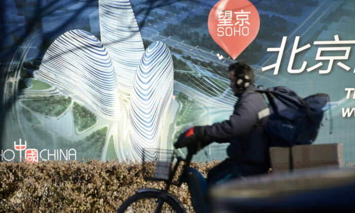 A Chinese man rides a tricycle past a billboard for the under-construction Wangjing SOHO complex by renowned architect Zaha Hadid in Beijing on Jan. 3, 2013. (Wang Zhao/AFP via Getty Images)