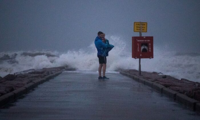 Local resident John Smith holds his 18-month-old son Owen as he stands near breaking waves on a pier ahead of the arrival of Tropical Storm Nicholas in Galveston, Texas, on Sept. 13, 2021. (Adrees Latif/Reuters)