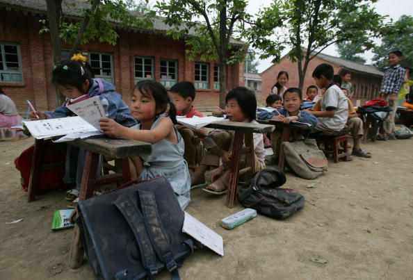Students study outdoors at a countryside primary school on May 22, 2007 in Huxian County of Shaanxi Province, China. Class is held outdoors for safety due to the schoolhouse being in danger of collapsing. In some rural areas of China, education still faces a lack of funding, good teachers, and stable facilities.  (Photo by China Photos/Getty Images)