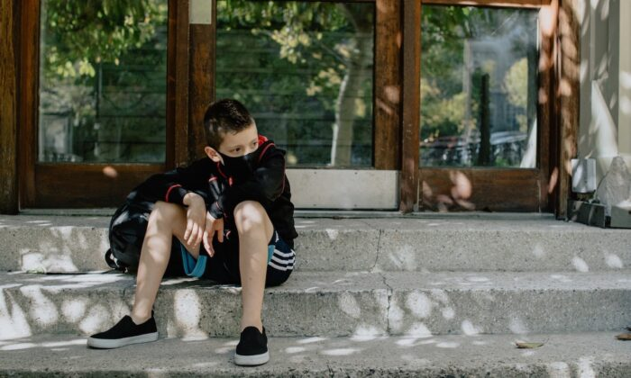 A boy wearing a mask sits on steps while waiting for school. (Kelly Sikkema/Unsplash)