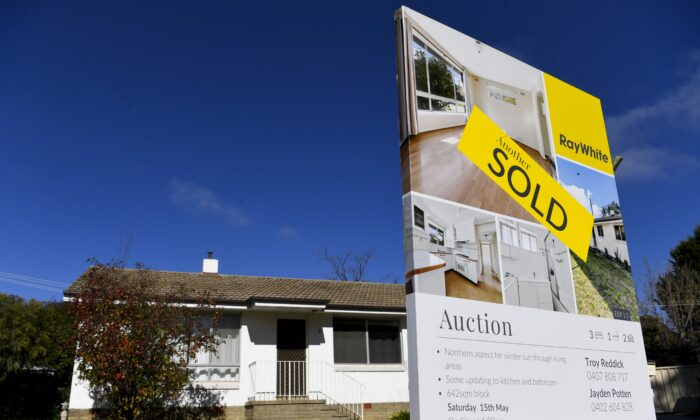 A 'SOLD' sticker is seen on a sale sign in front of a house in Canberra, Australia, May 18, 2021. (AAP Image/Lukas Coch)