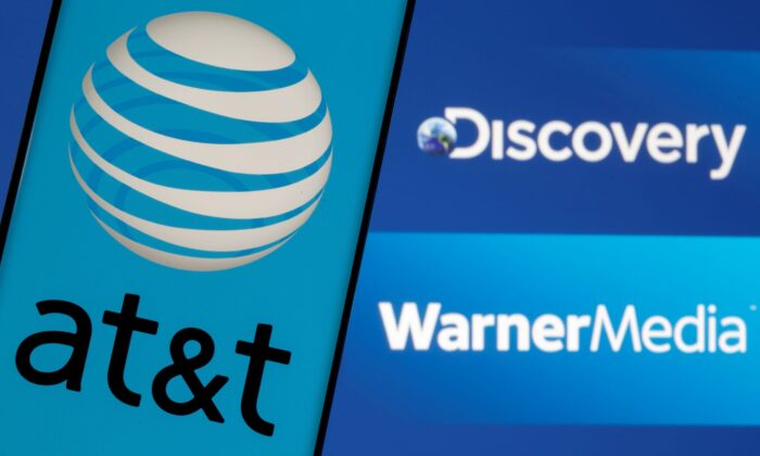 AT&T logo is seen on a smartphone in front of displayed Discovery and Warner Media logos in this illustration taken on May 17, 2021. (Dado Ruvic/Reuters)