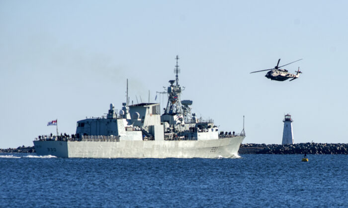 A Sikorsky CH-148 Cyclone flies around HMCS Halifax as the frigate leaves the harbour in Halifax on Jan. 1, 2021, to start a six-month deployment in the Mediterranean Sea to assist in NATO counter-terrorism patrols and related activities throughout the region. (The Canadian Press/Andrew Vaughan)