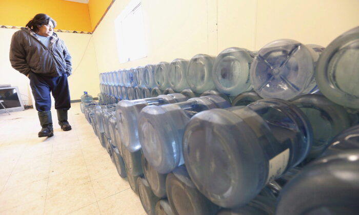 Stewart Redsky, former chief and current Alcohol/Drug Counsellor of Shoal Lake 40 First Nation, walks past one week's worth of 20 litre water bottles in the community's water storage room on Feb. 25, 2015. (The Canadian Press/John Woods)