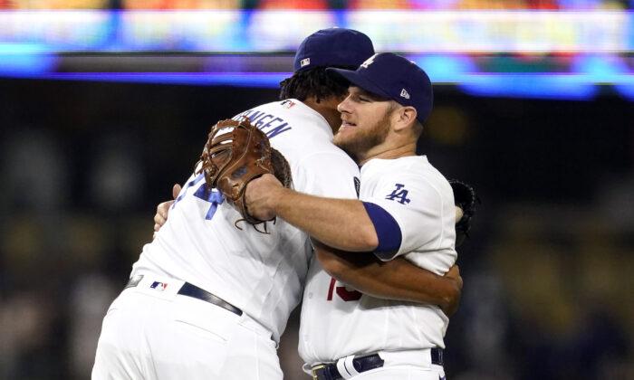 Los Angeles Dodgers relief pitcher Kenley Jansen, left, hugs Max Muncy after the Dodgers' 8-4 win over the Arizona Diamondbacks in a baseball game in Los Angeles on Sept. 14, 2021. (Marcio Jose Sanchez/AP Photo)