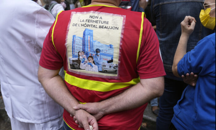 """A medical worker holds a placard reading: """"No at closing of the Beaujon Hospital,"""" during a protest gathering outside the Health Ministry, in Paris on Sept. 14, 2021. (Francois Mori/AP Photo)"""