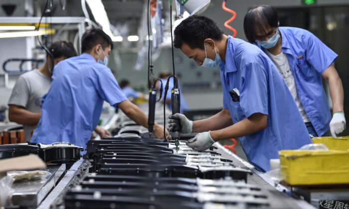 Workers produce washing machine parts at a factory in Nanjing, in China's eastern Jiangsu Province on Aug. 16, 2021. (STR/AFP)