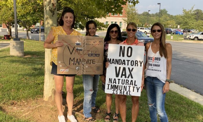 Michelle Friel (L), Lisa Hamm (2nd L), Heather Metz (2nd R), and Kelly Peter (R) protest outside the Loudoun County Public Schools administration building in Ashburn, Va., on Sept. 14, 2021. (Terri Wu/The Epoch Times)