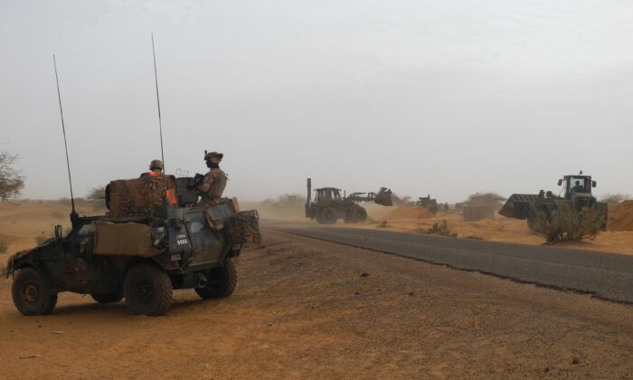 Two soldiers of the counter-terrorism Barkhane mission in Africa's Sahel region patrol aboard a Light Armored Vehicle (LAV) to observe the construction of the new French base in Gossi, center Mali, on March 25, 2019. (Daphne Benoit/AFP via Getty Images)