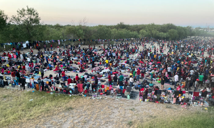 Thousands of illegal immigrants gather near the international bridge after crossing the Rio Grande, in Del Rio, Texas, on Sept. 16, 2021. (Charlotte Cuthbertson/The Epoch Times)