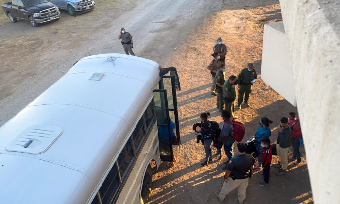 Illegal immigrants board a bus to be transported to a Border Patrol station for processing, under the international bridge, in Del Rio, Texas, on Sept. 16, 2021. (Charlotte Cuthbertson/The Epoch Times)
