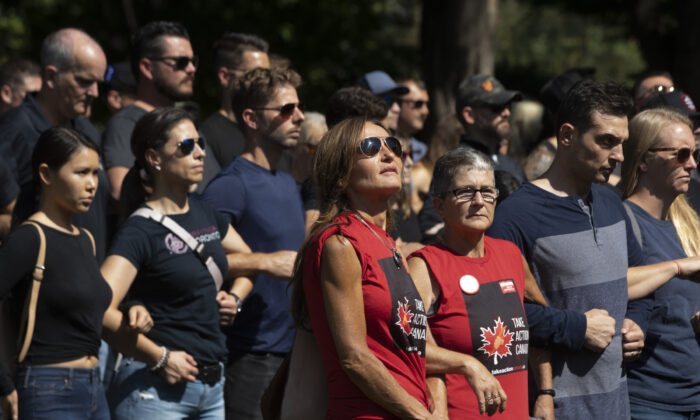 A group of front-line workers including healthcare professionals and members of the police and fire service protest vaccine mandates outside the Ontario Legislature in Toronto, on Sept. 13, 2021. (The Canadian Press/Darryl Dyck)