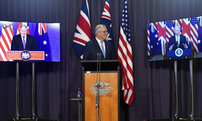 Australia's Prime Minister Scott Morrison (C) appears on stage with video links to Britain's Prime Minister Boris Johnson (L) and U.S. President Joe Biden at a joint press conference at Parliament House in Canberra, Australia, on Sept. 16, 2021. (Mick Tsikas/AAP Image via AP)