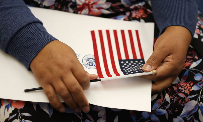 A person holds an American flag at a U.S. Citizenship & Immigration Services naturalization ceremony in Miami, Fl. on Aug. 17, 2018. (Joe Raedle/Getty Images)